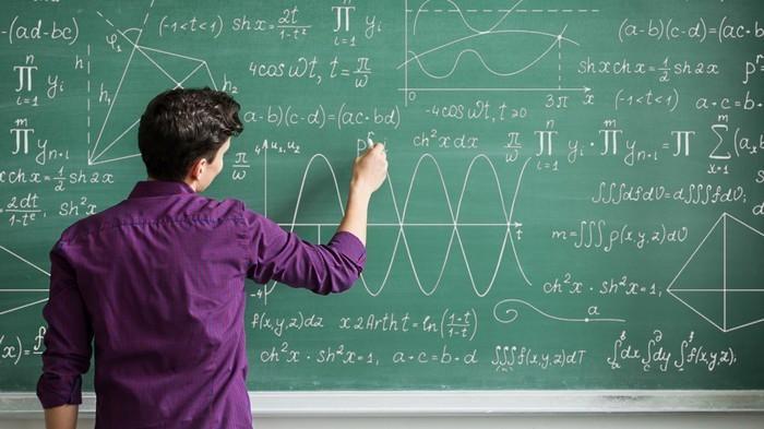 طالب يكتب على لوح أخضر رموز رياضيات